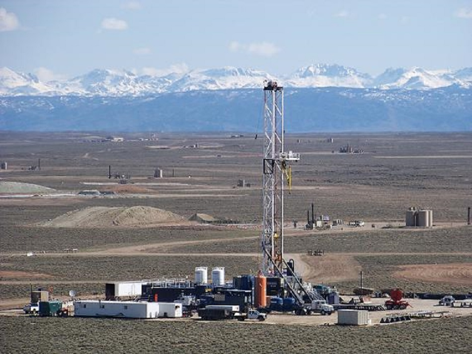 Photo of gas drilling rigs and well pads with Wind River Range, Wyoming in the background.