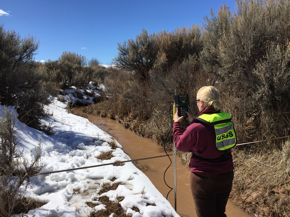 Photo of USGS hydrologist measuring streamflow in Dry Piney Creek, Wyoming during initial snowmelt.