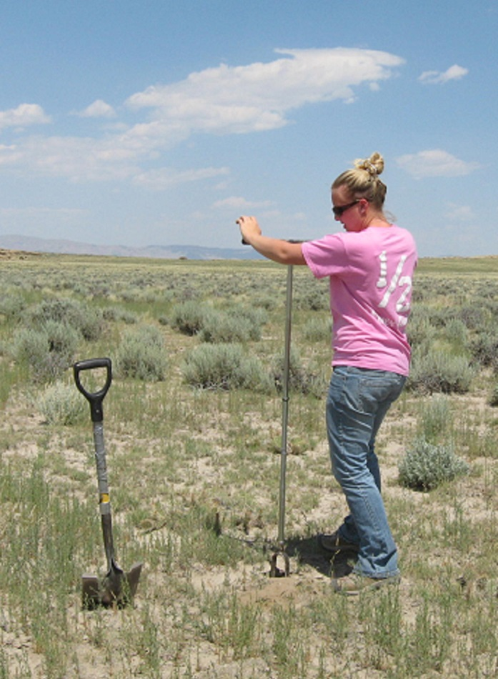 Photo of technician using hand auger to sample soils.